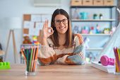 Young beautiful teacher woman wearing sweater and glasses sitting on desk at kindergarten smiling po poster