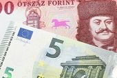 A Close Up Image Of A Red, One Hundred Hungarian Forint Bill Close Up With A Blue And Green Five Eur poster