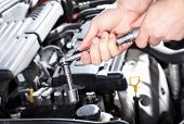 foto of internal combustion  - Hand of auto mechanic with a wrench - JPG