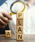 Wooden Blocks With The Word Plan And Magnifying Glass In The Hands Of A Businessman. Strategy Planni poster