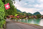 Swiss Flag Waving And Traditional Wood House And Boats On The Lake Brienz In Swiss Village Iseltwald poster