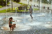 Children On A Sunny Warm Day Playing Outside In A Water Fountain. Children Happily In Shallow Clean poster