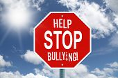 stock photo of disrespect  - Red help stop bullying stop sign on a beautiful sky and sunshine background - JPG