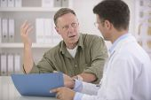 stock photo of angry  - Doctor talking to mature male patient - JPG