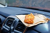Twisted Sugary Bun For Lunch. Sweet Snack On Console In Auto. Lunch Break While Traveling By Car. Ta poster