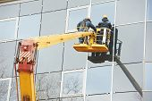 stock photo of millwright  - Tho builders worker installing glass windows on facade of business building - JPG