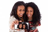 stock photo of two women taking cell phone  - Young black african american teenage girls taking pictures with cell phone isolated on white background  - JPG