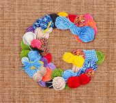 picture of g-string  - Letter G made of knitting yarn on burlap background - JPG
