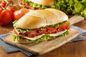 stock photo of deli  - Homemade Italian Sub Sandwich with Salami Tomato and Lettuce - JPG