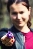 stock photo of hade  - Blurred young woman hading small bouquet of flowers - JPG
