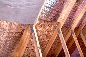stock photo of rafters  - Inside gable and joist view of ongoing project insulation of attic with fiberglass cold barrier and reflective heat barrier between the attic joists