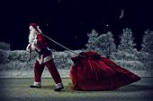 foto of heavy bag  - Santa Claus in a night winter forest pulling a huge bag of gifts - JPG
