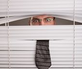 picture of blind man  - A young man looking through window blinds - JPG