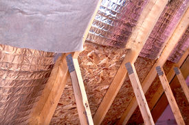 pic of gable-roof  - Inside gable and joist view of ongoing project insulation of attic with fiberglass cold barrier and reflective heat barrier between the attic joists  - JPG