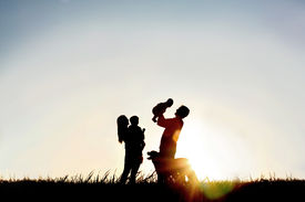 stock photo of four  - A silhouette of a happy family of four people mother father baby and child and their dog in front of a sunsetting sky with room four copy space or text - JPG