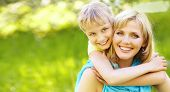 pic of hug  - hugging happy mother and daughter for a walk in the park on a light green background - JPG