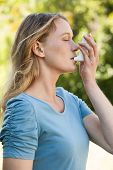 picture of inhalant  - Side view of a young woman using asthma inhaler at the park - JPG
