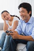 stock photo of ignorant  - Woman being ignored by boyfriend playing video games at home in the living room - JPG