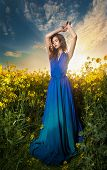 image of nightfall  - Fashion beautiful young woman in blue dress posing outdoor with cloudy dramatic sky in background - JPG