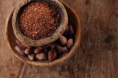 picture of cocoa beans  - cocoa beans and grated dark chocolate in old texured spoons bowls on wood - JPG
