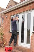 image of windows doors  - A Window fitter removing old windows and doors in preparation for new plastic ones to be fitted - JPG