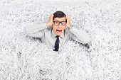 picture of terrifying  - Terrified man panicking in a pile of shredded paper  - JPG