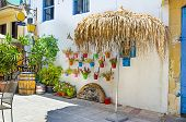 foto of larnaca  - The outdoor cafe decorated with flowers in colorfull pots and straw umbrellas for shade Larnaca Cyprus - JPG