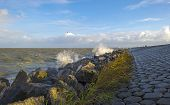 stock photo of dike  - Basalt stones along a dike in a stormy sea - JPG