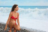 one joyful woman wearing swimsuit is sitting near water