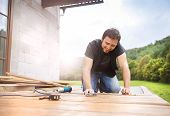 picture of hammer drill  - Smiling handyman installing wooden flooring in patio - JPG