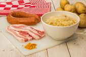 stock photo of pork belly  - Ingredients for typical dutch dish zuurkool with sauerkraut smoked sausage and pork belly - JPG
