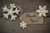 stock photo of ginger bread  - Brown Banner with Thank You on it and Ginger Bread Snowflakes with white Decoration on Wooden Background - JPG