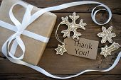 picture of ginger bread  - Thank You on a Tag with Christmas Decoration as a brown Gift and decorated Ginger Bread Cookies on Wooden Background - JPG