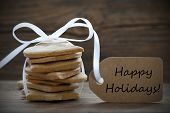 picture of ginger bread  - Ginger Bread Cookies with white Ribbon and Label with Happy Holidays on it on wooden Background - JPG