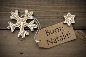 stock photo of ginger bread  - The Italian Words Buon Natale which means Merry Christmas on a Label with some Ginger Breads on Wood - JPG