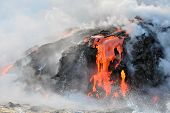 stock photo of magma  - Red and Orange magma flowing from Hawaiian volcano into the Pacific Ocean - JPG