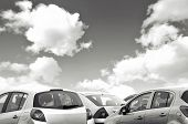 picture of polution  - Closeup view of parked cars with coudy sky in black and white - JPG