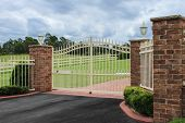 stock photo of driveway  - Driveway entrance gates to property set in brick wall  - JPG