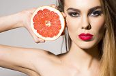 foto of pomelo  - Young woman holding grapefruit cut in half next to the head healthy life concept  - JPG