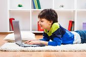 stock photo of pre-adolescent child  - Cute little boy is using laptop at his home - JPG