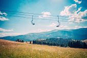 picture of lifting-off  - Emtpy chairlift in ski resort in summer with green grass and no snow - JPG