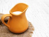 picture of pitcher  - milk in pitcher on a old wooden background - JPG