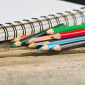stock photo of blank check  - Checked blank notebook with multicolored pencils on wood background
