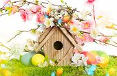 stock photo of leak  - Easter decoration with birdhouse and eggs on green grass - JPG