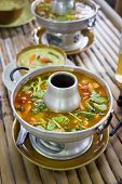 picture of gai  - Tom yum soup in traditional dishware in a street restaurant - JPG
