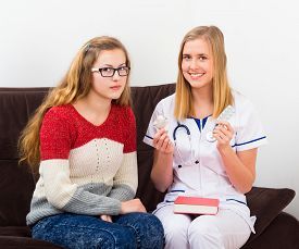 stock photo of contraception  - Gynecologist helping teenager with information on contraception - JPG