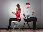 foto of not talking  - Couple using mobile phones not talking to each other - JPG
