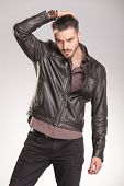 picture of down jacket  - Attactive young fashion man looking down while fixing his hair - JPG
