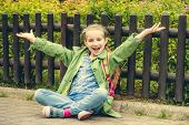 picture of schoolgirls  - Little pretty schoolgirl  sitting on the street with her backpack - JPG