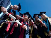 picture of graduation hat  - high school students graduates tossing up hats over blue sky - JPG